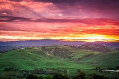 Hermosa vista de campos y de prados verdes en la puesta del sol en Toscana Foto de archivo libre de regalías
