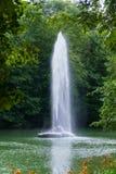 Hermosa vista de detrás el follaje verde de los árboles a la fuente en el medio de la charca con una corriente clara Fotografía de archivo libre de regalías