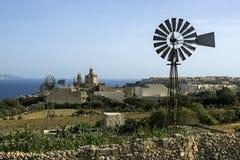 Hermosa vista de la costa maltesa en el día soleado claro, el mar, las casas hermosas y los molinoes de viento En un fondo el mar Fotografía de archivo libre de regalías