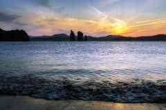 Hermosa vista de la puesta del sol sobre rocas en el mar imagen de archivo