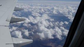 Hermosa vista de la tierra con las nubes de la porta del avión durante el vuelo almacen de metraje de vídeo