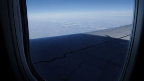 Hermosa vista de la tierra con las nubes de la porta del avión durante el vuelo metrajes