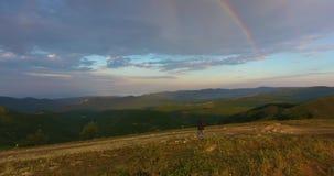 hermosa vista de montañas verdes bajas con el arco iris en cielo ilimitado almacen de metraje de vídeo