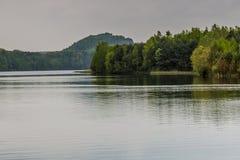 Hermosa vista de un lago con muchos árboles y un cielo gris foto de archivo libre de regalías