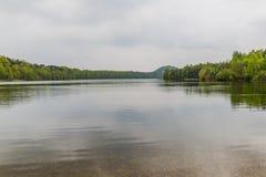 Hermosa vista de un lago con muchos árboles y un cielo gris y de la reflexión en el agua imagenes de archivo