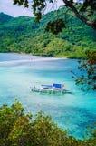 Hermosa vista de una serpiente tropical de la isla con los turistas llenos del barco tradicional blanco del banca EL Nido, Palawa Foto de archivo libre de regalías