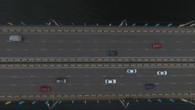 Hermosa vista del camino ancho del puente con muchos coches del montar a caballo en ella sobre el río oscuro almacen de video
