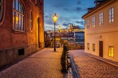 Hermosa vista del castillo de Praga en la puesta del sol de una calle histórica con las lámparas de gas sobre el río Moldava Fotografía de archivo libre de regalías