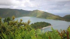 Hermosa vista del lago en las montañas que pasan por alto el océano y el bosque denso almacen de metraje de vídeo