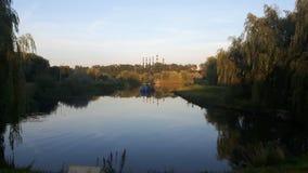 Hermosa vista del lago y de los edificios industriales fotos de archivo