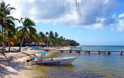 Hermosa vista del mar del Caribe, del mar azul, de un puente quebrado y de un barco de una playa arenosa con las sillas azules en imagen de archivo libre de regalías