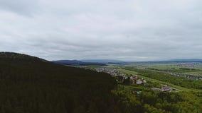 Hermosa vista del pie de la montaña y de una pequeña ciudad en el pie almacen de metraje de vídeo