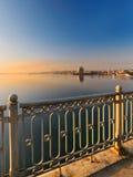 Hermosa vista del puente a la ciudad en el amanecer en los rayos del sol naciente Foto de archivo libre de regalías