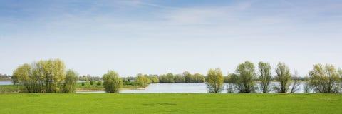 Hermosa vista en un paisaje holandés cerca del río Waal y Zaltbommel, agua, hierba verde, prados y árboles en un día soleado Foto de archivo libre de regalías