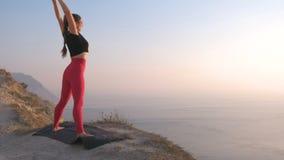 Hermosa vista la mujer que hace la yoga que estira en la montaña con la opinión del mar en la puesta del sol Estirando las manos  almacen de metraje de vídeo