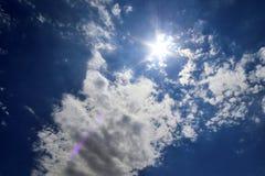 Hermosa vista sobre rayos de sol con algunas llamaradas de la lente y nubes en un cielo azul imágenes de archivo libres de regalías