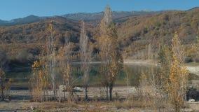 Hermosas vistas del lago cerca de las montañas y de los árboles tiro Paisaje asombroso del oto?o metrajes