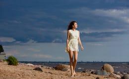 Hermoso adelgace a la muchacha descalza que camina en una playa contra el mar Fotos de archivo