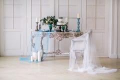 Hermoso adorne la tabla con las velas, el florero con las flores y el pastel de bodas en la tabla en estudio Imagenes de archivo