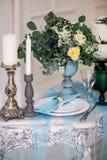 Hermoso adorne la tabla con las velas, el florero con las flores y el pastel de bodas en la tabla en estudio Foto de archivo