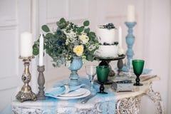 Hermoso adorne la tabla con las velas, el florero con las flores y el pastel de bodas en la tabla en estudio Foto de archivo libre de regalías