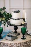 Hermoso adorne la tabla con las velas y el pastel de bodas en la tabla en estudio Foto de archivo