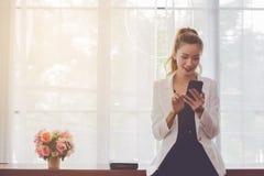 Hermoso asiático en el vestido blanco con la empresaria marrón larga del pelo que usa inicio elegante del teléfono está desarroll fotografía de archivo