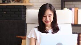 Hermoso de la mujer joven asiática del retrato que trabaja el ordenador portátil en línea con sonrisa y sentarse feliz y de risa