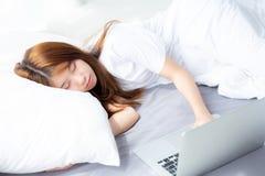 Hermoso de mujer asiática joven del retrato con el ordenador portátil que se acuesta en dormitorio Imagenes de archivo