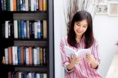 Hermoso de mujer asiática joven del retrato relaje el libro de lectura que se sienta en sala de estar en casa, literatura del est imagenes de archivo