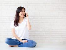 Hermoso del teléfono elegante y de la sonrisa de la charla asiática joven de la mujer del retrato que se sientan en fondo concret fotografía de archivo