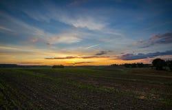 Hermoso después de cielo de la puesta del sol sobre campos Foto de archivo