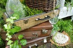 Hermoso diseño en el parque - maletas del vintage con las botellas, las placas y la cesta en hierba Fotos de archivo