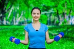 Hermoso, el atleta implicado en deportes en la calle, conduce el entrenamiento con pesas de gimnasia Imagen de archivo libre de regalías