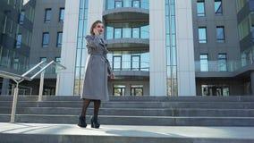 Hermoso, elegante, mujer de negocios que habla en el edificio de oficinas cercano al aire libre del teléfono Ella es una muy feli almacen de metraje de vídeo