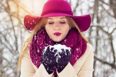 Hermoso, elegante y chica joven, soplando la nieve de sus manos Moda Foto de archivo