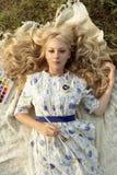 Hermoso encantando descalzo la pintura adolescente rizada larga del pelo rubio Fotos de archivo libres de regalías