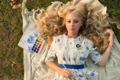 Hermoso encantando descalzo la pintura adolescente rizada larga del pelo rubio Foto de archivo