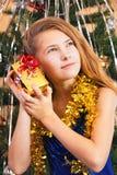 ` Hermoso feliz s de la muchacha del adolescente que sacude su regalo de Navidad Fotografía de archivo