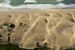 Hermoso luz las dunas de arena que corrían en el mar hecho a mano por los fuertes vientos imagen de archivo