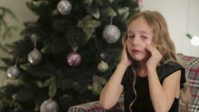 Hermoso, niña sentándose y llorando en el fondo del árbol de navidad almacen de video