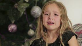 Hermoso, niña sentándose y llorando en el fondo del árbol de navidad almacen de metraje de vídeo
