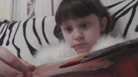 ` Hermoso s de la niña que entrena para tocar la guitarra almacen de metraje de vídeo
