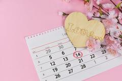 Hermoso un corazón de madera con las flores rosadas en un fondo rosado Imagen de archivo libre de regalías
