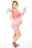 Hermoso una muchacha embarazada con los zapatos de bebé Fotos de archivo