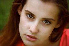 Hermoso y chica joven que se sientan en el grassGirl con una mirada confiada Fotos de archivo libres de regalías