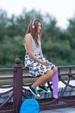 Hermoso y forme a la mujer joven que presenta con el monopatín, verano, urbano, Foto de archivo libre de regalías