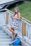 Hermoso y forme a la mujer joven que presenta con el monopatín, verano, urbano, Fotografía de archivo