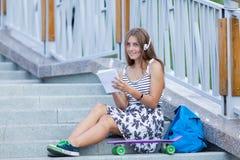 Hermoso y forme a la mujer joven que presenta con el monopatín, verano, urbano, Fotos de archivo