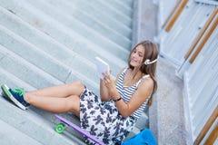 Hermoso y forme a la mujer joven que presenta con el monopatín, verano, urbano, Imagen de archivo libre de regalías